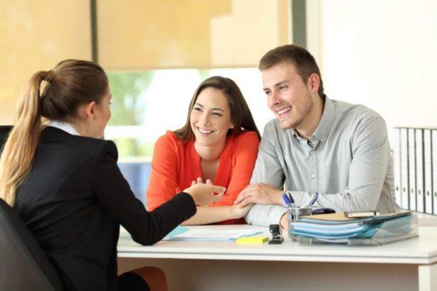 Casal de possíveis colaboradores felizes enquanto conversam com mulher de terno.